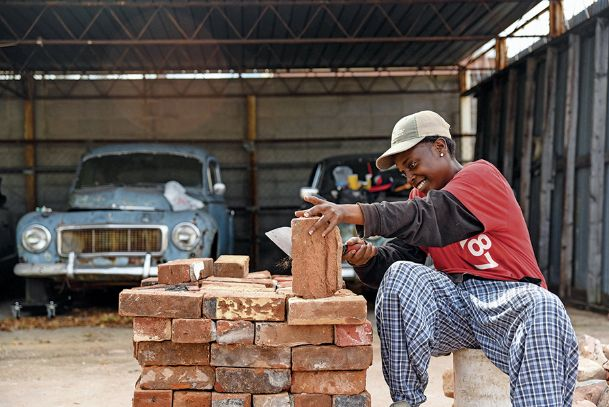 Jataune James sorts and cleans bricks at Waukaway Springs in Columbus Tuesday afternoon. Waukaway Springs is being restored to its former look. The building formerly housed Brown Buick Company.