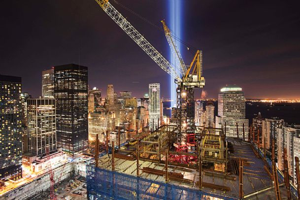 """The """"Tribute in Light� shines above the construction cranes on One World Trade Center and the lower New York skyline in this Sept. 11, 2010 file photo. The spire was fully installed atop One World Trade Center on Friday, bringing the New York City structure to its symbolic height of 1,776 feet."""