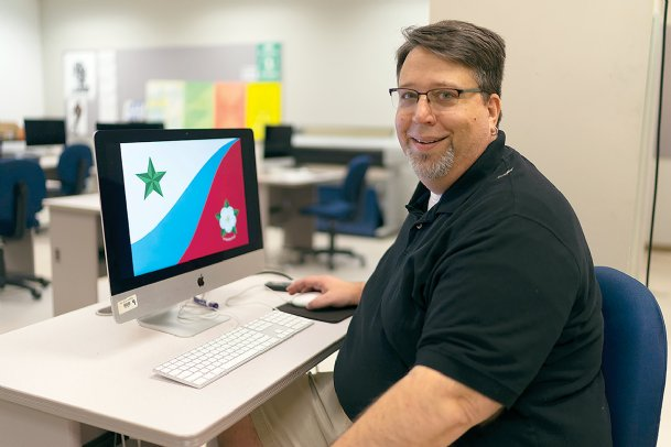 Citizens from across Mississippi answered the call to submit suggested designs for Mississippi's new flag. Jim McAnally, who teaches graphic design at The W, is pictured Friday with his.