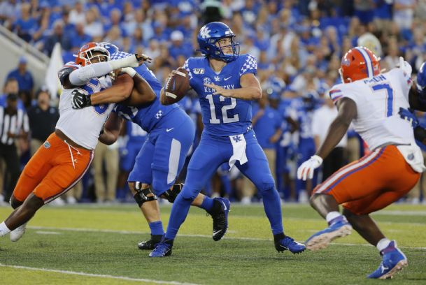 Kentucky Wildcats quarterback Sawyer Smith (12) passes the ball against Florida Gators linebacker Jeremiah Moon (7) in the first quarter at Kroger Field.
