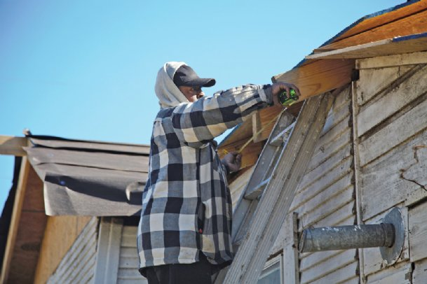 Willie Peterson, a carpenter of 17 years, measures a house roof that he's repairing on Shady Street on Friday afternoon. He's preparing the roof for new shingles to be installed on Saturday, he said. The house is one of several on the street damaged or destroyed by a Feb. 23, 2019, tornado on which repairs have still not been completed.