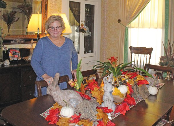 Lee Hackett shows off her dining room table, decorated in the spirit of fall by her lifelong friend Tee Pittman, at her home in Columbus on Thursday. Pittman decorated the table last week after Hackett's knee replacement surgery temporarily limited her mobility. The two women have been friends for decades, and both are survivors of a form of breast cancer called ductal carcinoma in situ (DCIS), from which they recovered without having chemotherapy.