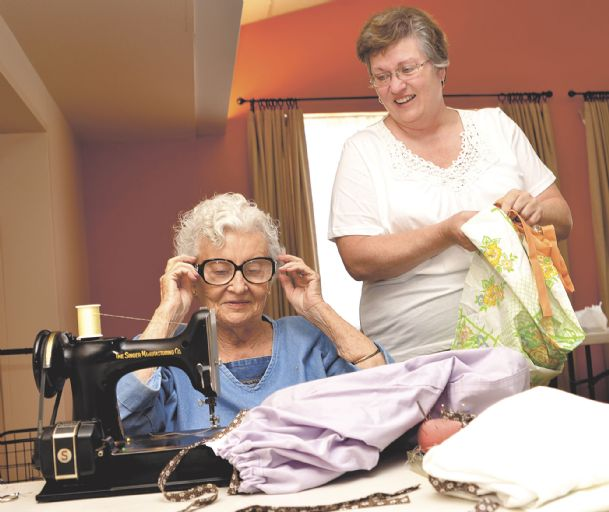 """Deacon Pam Rhea looks on as seamstress Bettye Jane Kerby prepares to sew colorful straps on dresses made from pillowcases June 16 at St. Paul's Episcopal Church in Columbus. Kerby and Rhea were among volunteers at a workday for the """"Little Dresses for Africa� project."""