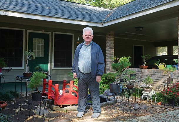 John Weathers of Columbus is pictured outside his west Lowndes County home Thursday with a few of the dozens of bonsai trees he has in various stages of development. Weathers took up bonsai seriously about 12 years ago after moving to Columbus from the Gulf Coast. Each tree requires years of patient pruning, repotting and shaping.