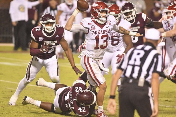Arkansas Razorbacks quarterback Feleipe Franks (13) makes a pass as he is hit by Mississippi State Bulldogs defensive end Marquiss Spencer (42) during the fourth quarter on Oct. 3 at Davis Wade Stadium at Scott Field.