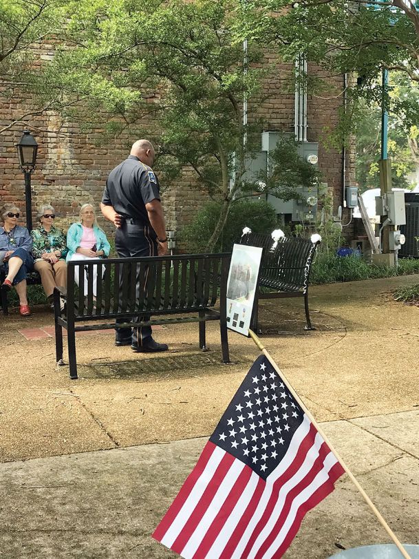 Aberdeen Assistant Police Chief Quinell Shumpert pays respects to the late Johnny Buster at Leadership Plaza in downtown Columbus Aug. 10. Johnny's wife, Patsy, dedicated a bench to honor Johnny's 22 years in the U.S. Air Force and 18 years as a police officer with Aberdeen.