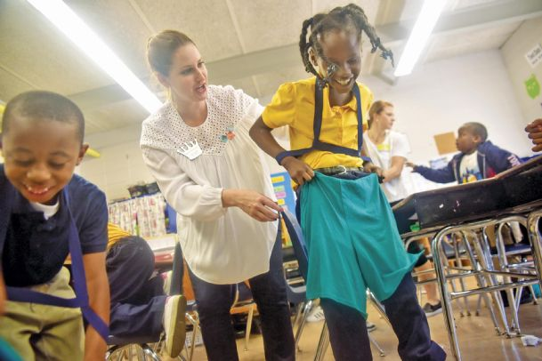 Junior Auxiliary member Alicia Truesdale helps Joe Cook Elementary student Candice Billups, 8, feel as though she can better put herself in a disabled person's shoes Wednesday. By hindering her arm extension to do a simple task, such as put on shorts, Candice got a glimpse at how being a person with cerebral palsy would feel. Candice is the daughter of Connie Billups of Columbus.