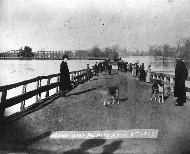 Flood waters in 1892 crossing over the Tombigbee Bridge at Columbus. This bridge was at the foot of Main Street where the vehicle bridge to the Island is now located.