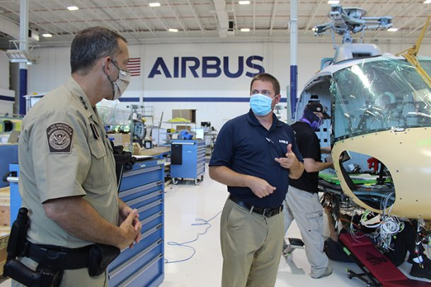 Deputy Executive Assistant Commissioner of Policy for Air and Marine Operations at U.S. Customs and Border Protection Steve Boyer, left, speaks with Airbus Senior Manager of Industry Troy Ham while Airbus employees work on a CBP helicopter at the company's Lowndes County facility on Wednesday. CBP ordered 16 specially-made H125 helicopters from Airbus, the first of which has already been delivered, and the last of which will be delivered in October 2021.
