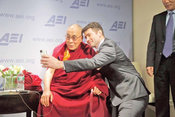 "Tibetan spiritual leader the Dalai Lama poses for a ""selfie� with blogger and activist Alek Boyd during a break between panel discussions at an event entitled: ""Happiness, Free Enterprise, and Human Flourishing� on Thursday at the American Enterprise Institute in Washington."