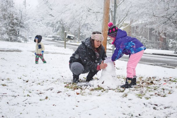 Courtney Leveck, center, builds a snowman with her children, Lydia, 6, right, and Harlan, 2, left, in front of their house on Critz Street in Starkville this morning. Lydia has seen a snowfall like today's before, her mother said, but Harlan has not. The National Weather Service indicated snow accumulation in the area could exceed two inches by mid-day, but temperatures are expected to rise to nearly 40 later today.