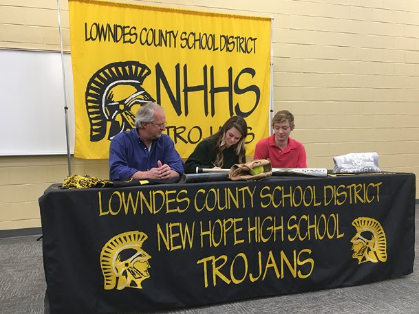 New Hope senior Charly Clanton signs her letter of intent to Northeast Mississippi Community College on Wednesday. Clanton's father Richard and brother Caston look on.