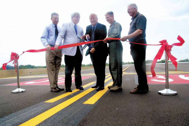 From left, David Shumate, Bobby Harper, Mike Hainsey, Col. Barre Seguin and Duanne Burns cut the ribbon to the airstrip extension on Landing Road at the Golden Triangle Regional Airport, Thursday.