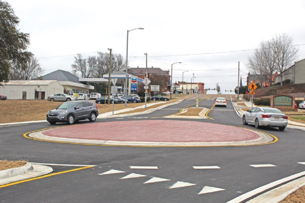 Cars go through the new roundabout on Main Street in front of Harvey's on Friday afternoon. The city of Columbus opened the roundabout Friday morning. The Mississippi Department of Transportation paid 80 percent of the almost $800,000 project.