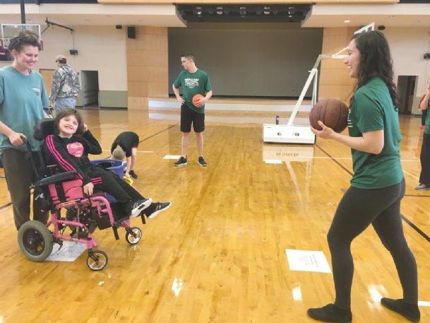 Jenna Sullivan, 17, far left, holds the wheelchair of her sister, 13-year-old Mary Margaret Sullivan, as Mary Margaret plays catch with volunteer Elizabeth Carranza on Sunday at the Starkville Sportsplex.