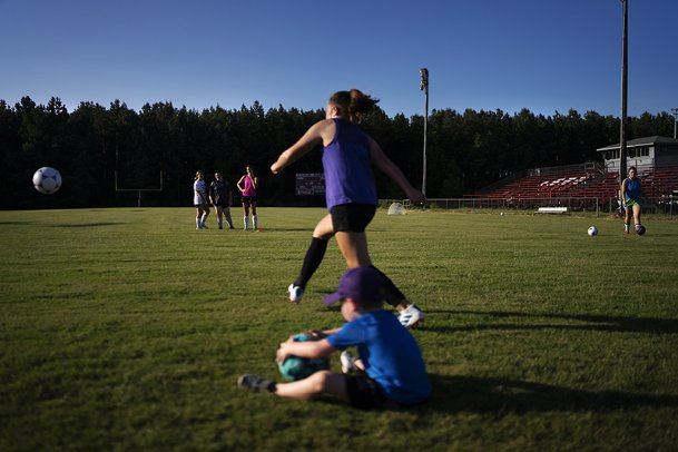 Cassie Carter kicks the ball during a drill as Ridge Swain, bottom middle, 5, plays with a ball during soccer practice on July 16 at Columbus Christian Academy.