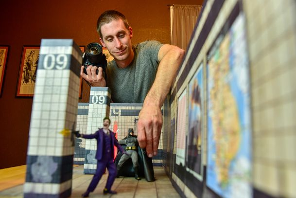 Erik Studdard sets up a photograph Tuesday, positioning a 25th anniversary Michael Keaton Batman and The Joker against the backdrop of an abandoned Gotham City subway terminal. The one-twelfth scale figures come with different head sculpts and hand sculpts that allow toy photographers like Studdard to tell stories through different scenes. Studdard, who lives near downtown Columbus, is a graphic designer at Nicholas Air.