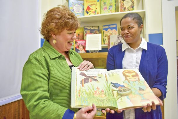 """Oktibbeha County Heritage Museum board member Hellen Polk, left, and museum volunteer Shamera Brumfield look through """"Birds,� a 1958 Little Golden Book by Jane Werner Watson, with iconic illustrations by Eloise Wilkin. Polk's collection of Golden Books is at the museum through mid-March. The books introduced in 1942 are a touchstone for generations of readers. The Smithsonian Institution includes Little Golden Books and artwork in its Division of Cultural History."""