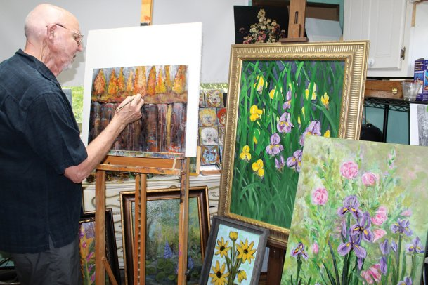 When planned travels were canceled due to COVID-19, Ralph Null, pictured Wednesday in his Columbus home studio, took to the canvas as a way to stay occupied and channel creativity. He has emerged with almost 180 paintings that will be shown at the Columbus Arts Council's Rosenzweig Arts Center throughout September. A public reception is 5:30-7 p.m. Thursday. Null will also give
