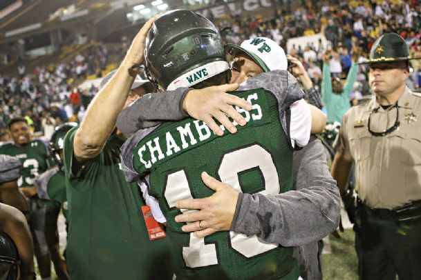 West Point High School football coach Chris Chambless hugs his son, Jake, after the Green Wave defeated West Jones 27-12 in the Mississippi High School Activities Association (MHSAA) Class 5A State Championship Game on Saturday at Southern Mississippi's M.M. Roberts Stadium in Hattiesburg.
