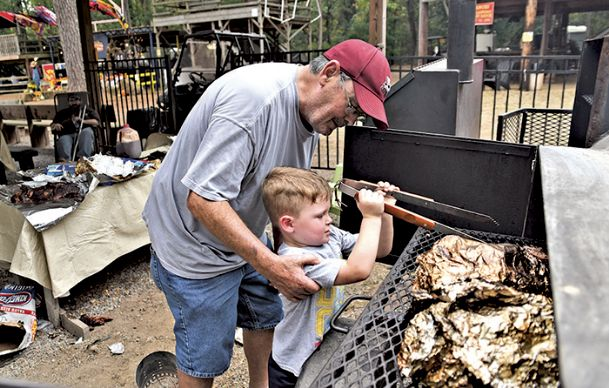 Joe Langford helps his grandson Rhett Hall, 3, take meat off of the grill in this file  photo from 2017 Roast-n-Boast. The festival may go without funds from the 2-percent tourism sales tax for this year's event.