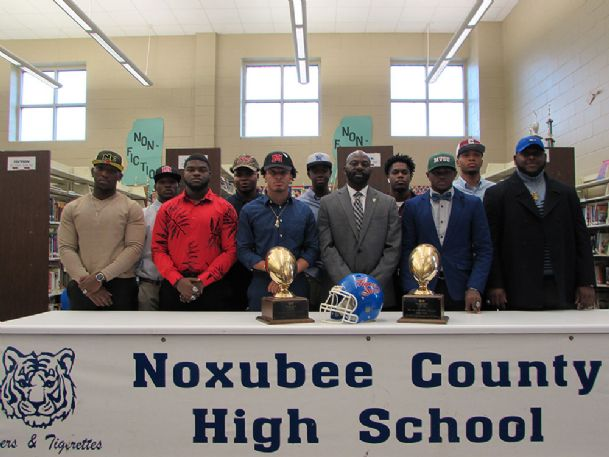 Former Noxubee County High School football coach Tyrone Shorter poses for a picture with 10 of the players from his 2018 team who signed Wednesday to play football in college during a ceremony in the school's library.