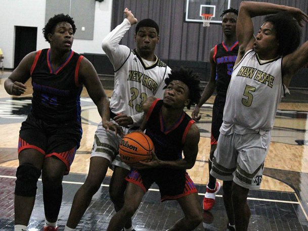 Noxubee County senior Sam Sledge (2) goes up for a layup while being defended by New Hope juniors Caleb Parr (23) and Ty Crowell (5) in the third quarter of Tuesday's game at New Hope. The Tigers lost 75-67.