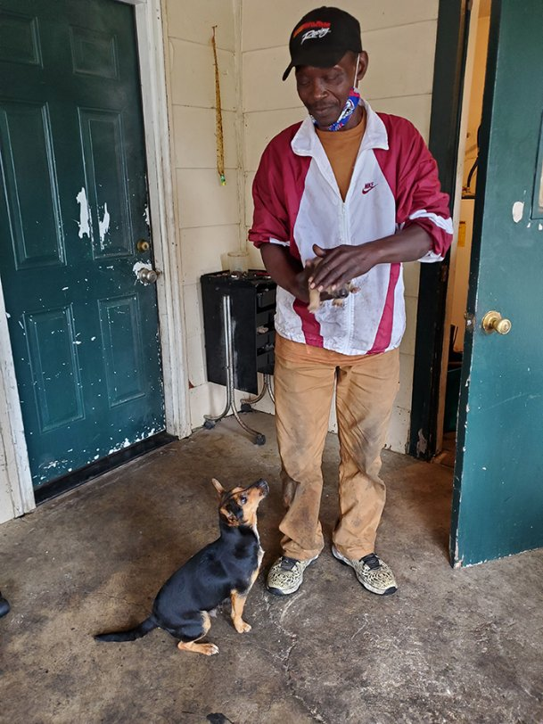 James Winder holds one of his dog Lady's three puppies at his house in Oktibbeha County on Thursday. He said Lady is very protective of her puppies, her second litter in four years, and will let almost no one near them.