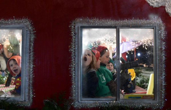 Nicholas Edwards, 7, left, son of David and Samantha Edwards and Elliot Lewis, 5, right, son of Ryan and Haley Lewis look out the windows of the Boy Scouts float while waiting for the Columbus Christmas Parade to begin on Dec. 2 by the Columbus Soccer Complex. / Photo by: Jennifer Mosbrucker/Dispatch Staff