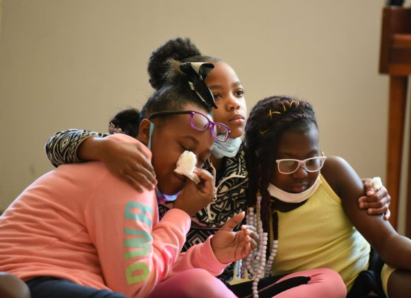 From left, Allyson Henley, 10, Alhyson Jett, 9, and Kylah Neely, 10, comfort each other and wait for prayers to conclude during Ms. Smith's Academic Summer Camp on July 23 at the Needmore Center in Starkville. Community leaders led a prayer circle for the campers and then offered to pray for with the kids individually about anything that was on their minds. Allyson, Alhyson and Kylah each received prayers and then sat down together while the rest of their peers were prayed over. / Photo by: Claire Hassler/Dispatch Staff