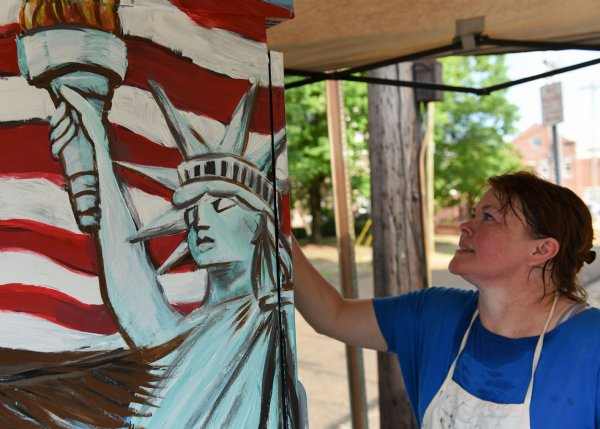 Amy Ballard paints the utility box at the intersection of Main Street and 6th Street on July 16 in Columbus. Ballard painted the utility box in front of the post office and city hall, so she knew she wanted to make it something patriotic. / Photo by: Claire Hassler/Dispatch Staff