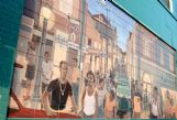 "The mural is designed to represent Catfish Alley from the 1920s through the late 1960s, when it was at its most vibrant. Buildings, cars and dress ""go back in time� as the painting recedes. A likeness in the doorway of the Ned Hardin Appliance Store at right represents the late Sallie Mae Jones, who opened Jones Restaurant in the Alley almost 70 years ago."