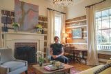 Julie Tompkins sits in the front sitting room of her home on Fifth Avenue South Tuesday. Log beams are original to the structure built in the 1820s and added on to.