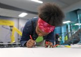 Jahmyah Jones, 14, sketches at the JBHM Architecture booth during the FORGE Foundation career expo on Wednesday at East Mississippi Community College's Communiversity. Jones is in the eighth grade at Columbus Middle School.