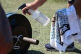 Assistant coach Tri Nason sprays weights with sanitizer during football practice on Thursday at Starkville High School. Nason said that the team must clean the weights between each group rotation and any time two players are sharing a set.