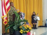 Col. Rodney Harris, left, presents the Mississippi National Guard's first Distinguished Teacher of the Year award to Niki Mulrooney, second from right, at Overstreet Elementary School's annual Veterans Day assembly on Wednesday. Armstrong Middle School sixth-grader Hannah Leach, right, nominated Mulrooney for her kindness and constructive classroom environment last year, during Hannah's stepfather's 14-month deployment.
