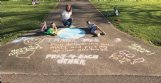 Mott Duncan Ellis and her grandchildren Lindsey Ruth Clark, left, and John Ross Dale, both 10, create encouraging messages in chalk at the end of Ellis' drive in Lowndes County.