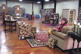 Tina Bivens, retail clerk at Again and Again Books, is pictured in one of the comfortable seating areas inside the shop dealing in gently-read books.