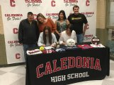 Caledonia seniors Maddy Suggs (front left) and Camryn Johnson sign their letters of intent to play volleyball at the Mississippi University for Women on Friday at Caledonia High School.