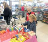Kroger greeter Ann Wozniak encourages Emalyn Deola, 7, to choose among the free snacks the store offers to children on Friday afternoon. Wozniak said her work as a greeter allows her to spend times with kids, something the grandmother of seven has always enjoyed.