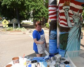 Amy Ballard paints the utility box at the intersection of Main Street and 6th Street on July 16 in Columbus.  Ballard describes her style of painting as serious and realistic. / Photo by: Claire Hassler/Dispatch Staff