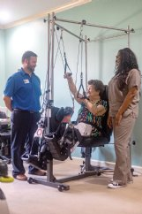 Peggy Cantelou spends time on the Quadriciser at The Arrington at Plantation Pointe in Columbus this past June. Director of Rehabilitation Will Davis, left, and physical therapy tech Keisha Hill look on. Plantation Pointe has three of the robotic rehabilitation therapy systems on its campus, for use by residents and others referred by physicians.