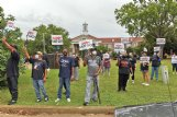 People hold signs and watch the back entrance of the courthouse during a protest demanding District 1 Supervisor Harry Sanders' resignation on Tuesday outside the Lowndes County Courthouse. The demands were in response to Sanders telling The Dispatch after the June 15 supervisors meeting that African Americans have been