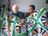 Lorene Thrasher, left, and her daughter-in-law, Glenda Thrasher, share memories about one of the many quilts Lorene has hand-stitched and given to members of her family.