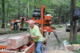 Mark Henry shifts the center cut from an oak log down the sawmill. Soon after, he and Cameron Scott used chains and a tractor with a front-end loader to move the 9-by-9-inch, 10-foot long column to the drying stack. The columns are for a customer's front porch.