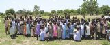 """Wearing new pillowcase dresses, girls from an African village wave their thanks for the gifts from """"Little Dresses for Africa,� a nation-wide nonprofit organization."""