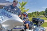 Columbus Police officer Chris Blaylock shows Sawyer Foster, 2, all the gadgets on a police motorcycle during the United Way of Lowndes County's Little Hands, Big Trucks event at the Soccer Complex in Columbus Saturday morning. Sawyer is the son of Zach and Kelli Foster.