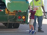 Collins Robertson, 3, pulls the lever on a garbage truck during the United Way of Lowndes County's Little Hands, Big Trucks event at the Soccer Complex in Columbus Saturday morning.
