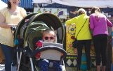 Luisa Porter/Dispatch Staff    Hailey Snell, 2, rides with her sunglasses in her stroller Saturday during the downtown Market Street Festival with her mother, Christina Snell of Columbus. Looking at art work behind them is Teresa Proffitt and Brittany Long of Columbus.