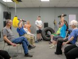 Salem Gibson, standing, leads the Rock Steady Boxing class in a strength and cognition exercise. Participants take turns holding a 10-pound weight above their heads while each person answers a question posed to the group.